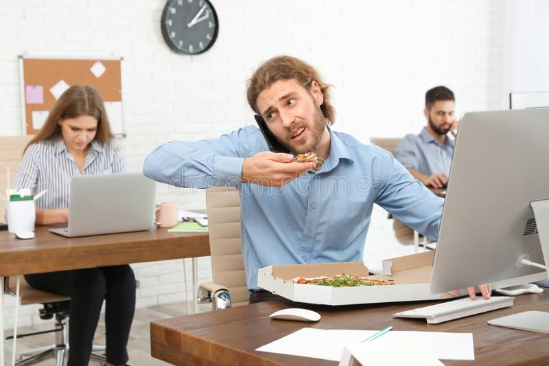 Office employee having pizza for lunch while talking on phone at workplace. Food delivery stock image