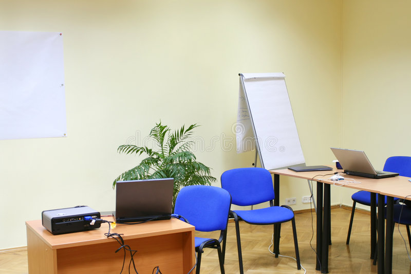 Office environment (laptop, blackboard, chairs). Empty office environment (laptop, flip chart, chairs, blackboard royalty free stock image