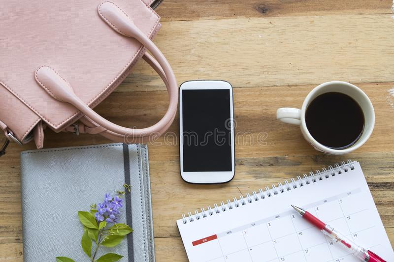 Office equipment for business work at office desk. Notebook planner, mobile phone and pink bag of lifestyle working woman for business at office desk on stock photos