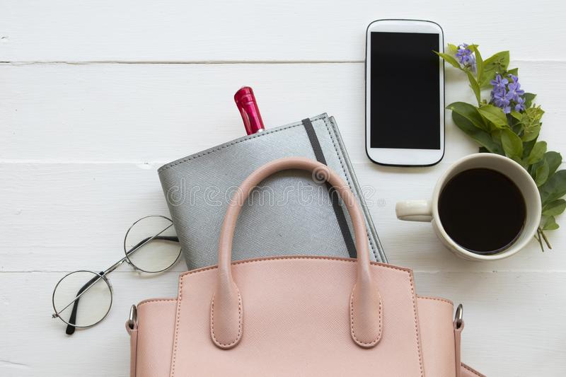 Office equipment for business work at office desk. Notebook planner, mobile phone and pink bag of lifestyle working woman for business at office desk on royalty free stock photo