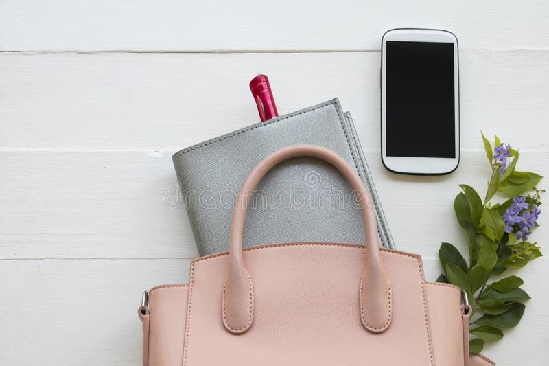 Office equipment for business work at office desk. Notebook planner, mobile phone and pink bag of lifestyle working woman for business at office desk on royalty free stock photography