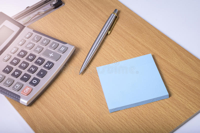 Office equipment. Paper note, pen and calculator on writing board at office in the morning warm light royalty free stock image