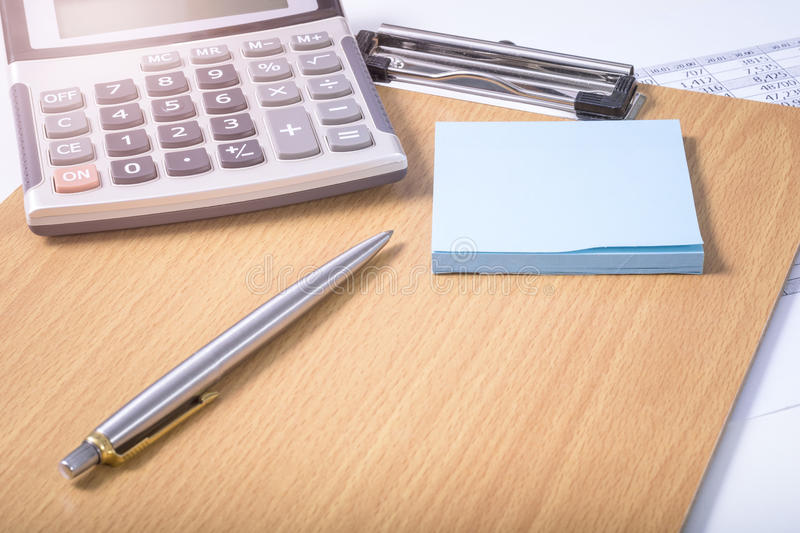 Office equipment. Paper note, pen and calculator on writing board at office in the morning warm light royalty free stock photo