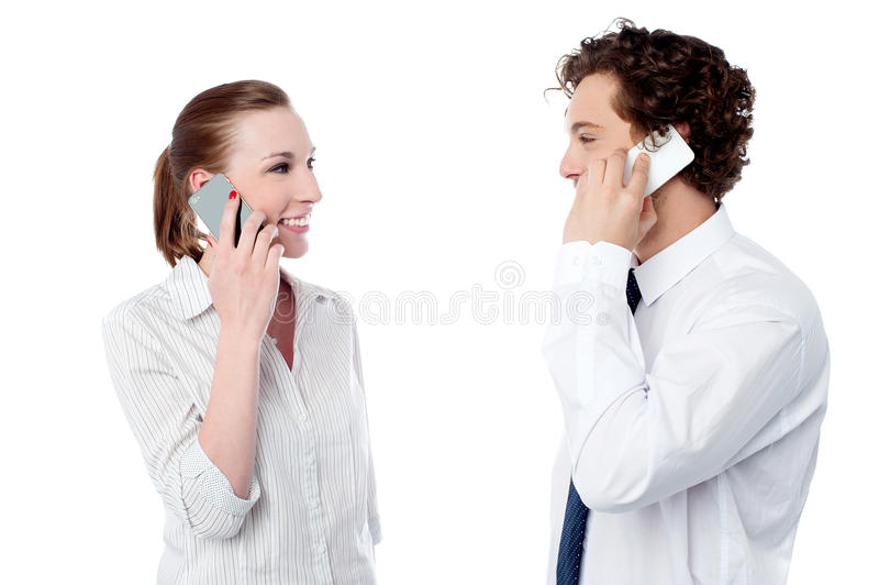 Office executives engaged over a phone call. Young office colleagues communicating over cellphone stock images