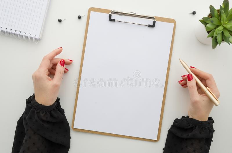 Office fashion concept. Flat lay clipboard mockup template paperwork. Female hands hold pen. Workplace. royalty free stock photos