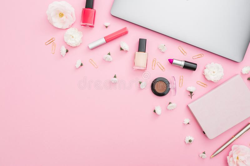 Office feminine desk with laptop, notebook, cosmetics and flowers on pink background. Top view. Flat lay concept. stock photo