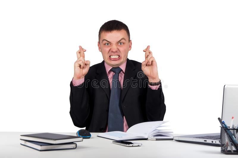 Wishing businessman crossing his fingers in his office isolated on white background stock photos