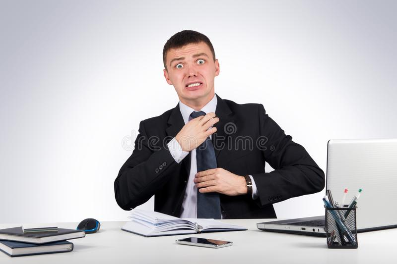 Frustrated businessman screams and pulls at his tie royalty free stock photography