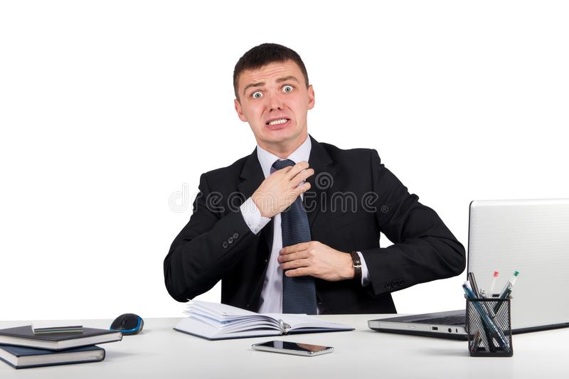 Frustrated businessman screams and pulls at his tie stock photography