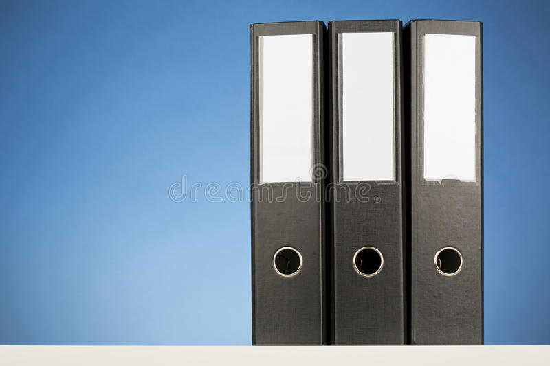 Office Folders. Three black business folders with blue background royalty free stock images