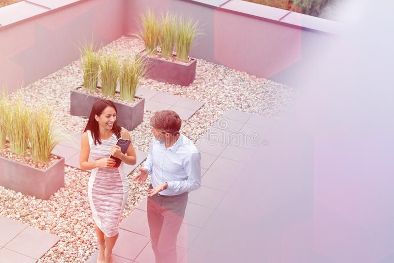 High angle view of smiling professionals talking at office terrace royalty free stock images
