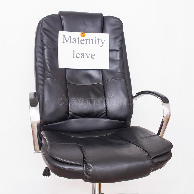 Office leather chair on which the inscription maternity leave. Childcare leave concept and dikret in the workplace stock image