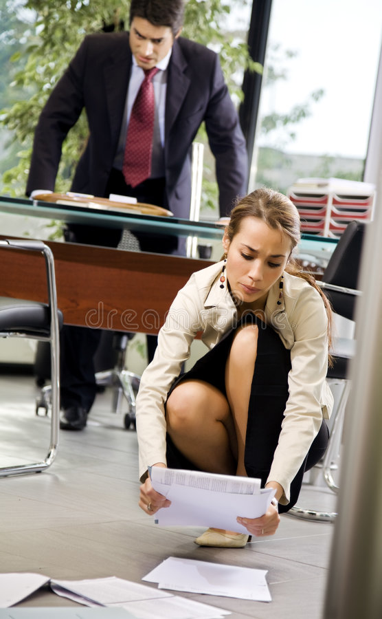 Office life. Exhausted secretary picking up some files stock photography