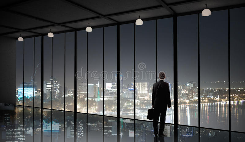 Office life. Businessman standing with back and looking in office window stock photography