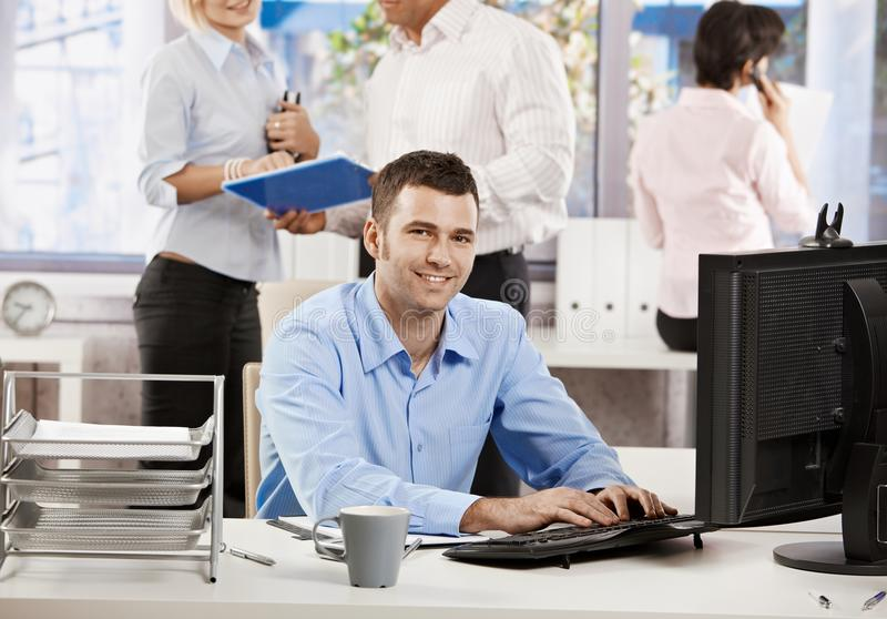 Office life - businessman working at desk stock photography