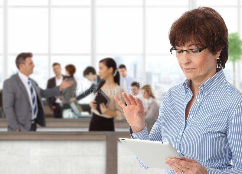 Office life businesswoman with tablet. Office life senior businesswoman with tablet royalty free stock image