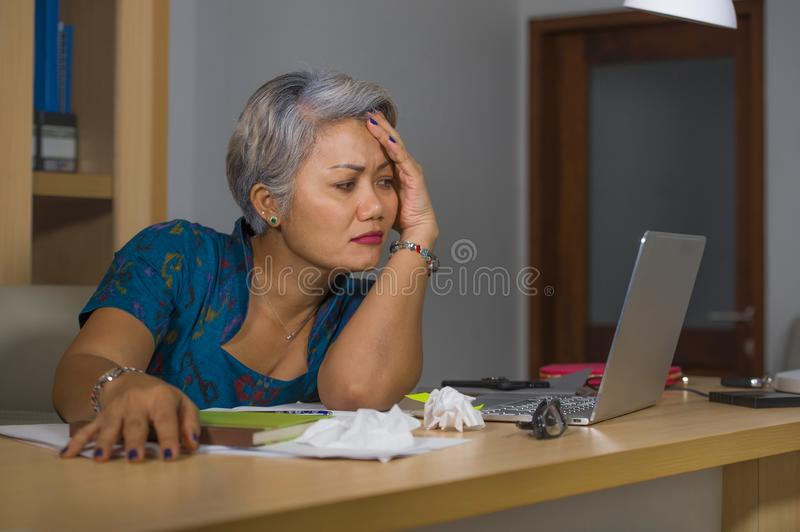 Office lifestyle portrait of sad and depressed middle aged attractive Asian woman working on laptop computer desk stressed and stock images