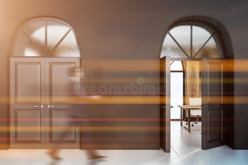 Gray office lobby with open door, man. Office lobby with black walls, white floor and two massive doors. One door is open and showing wooden wall room with table royalty free stock images