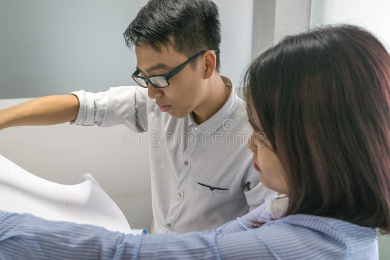 Office man and woman looking at project drawing paper stock photography
