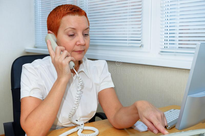 Office Manager girl dials the phone number . Thoughtful expression.  stock photos