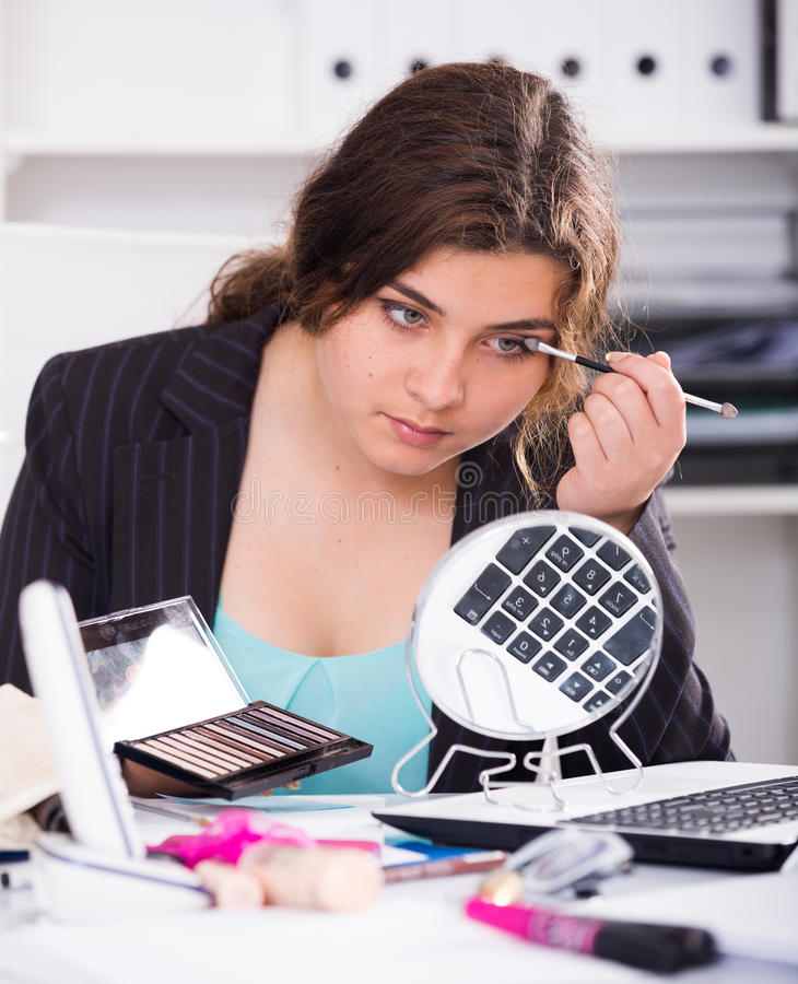 Office manager woman is making makeup before meeting royalty free stock photography