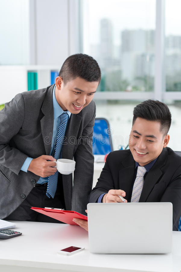 Office managers. Office manager showing something on the laptop to his colleague royalty free stock images