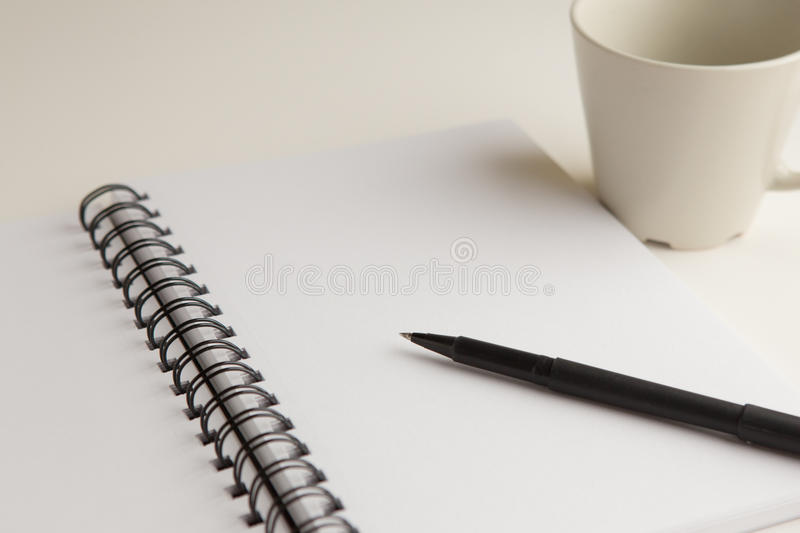 Office materials. A note pad, pen and mug on white royalty free stock photos