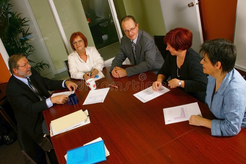 Office meeting. A group of office workers sit at a conference table, having a work meeting royalty free stock photo