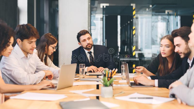 Young business team with male boss discussing work in office stock images