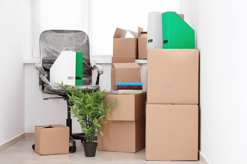 Office move concept. Carton boxes and chair. On floor in empty room stock image