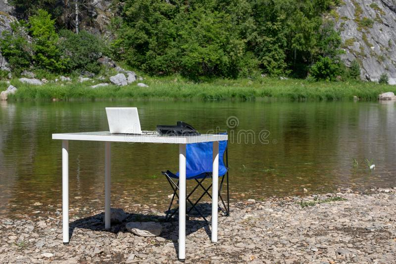 Office on nature. outdoor workplace. computer, phone and table. Remote work and earning online. Office on the nature. outdoor workplace. computer, phone and royalty free stock images