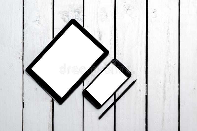 Office objects, devices with blank screens. White screen on smartphone and tablet on wooden table royalty free stock photography