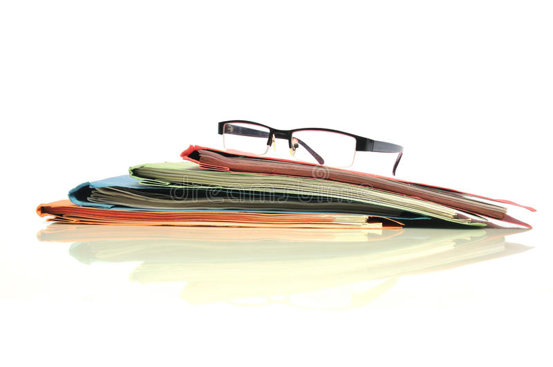 Office paperwork. Stack of multicolored folders with glasses royalty free stock photography