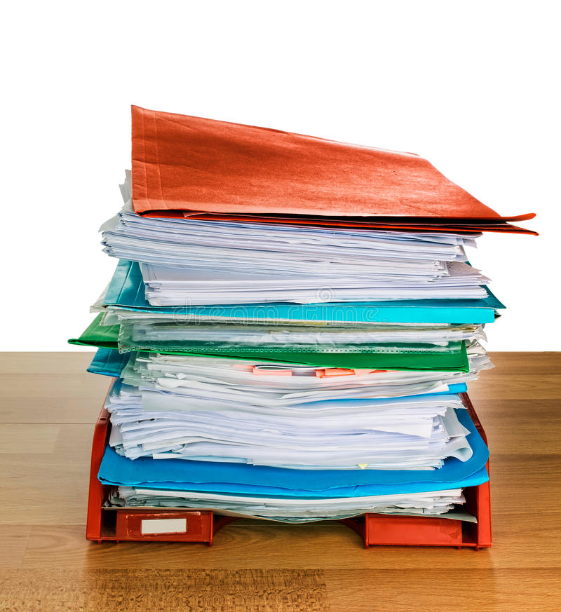 Office paperwork in-tray, administration. Lots of work! Piled up in tray with folders etc. White background royalty free stock images