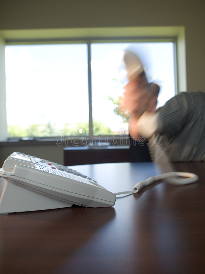 Office phone3. Motion blur of hand picking up or slamming down phone reciever. Large window in background stock photography