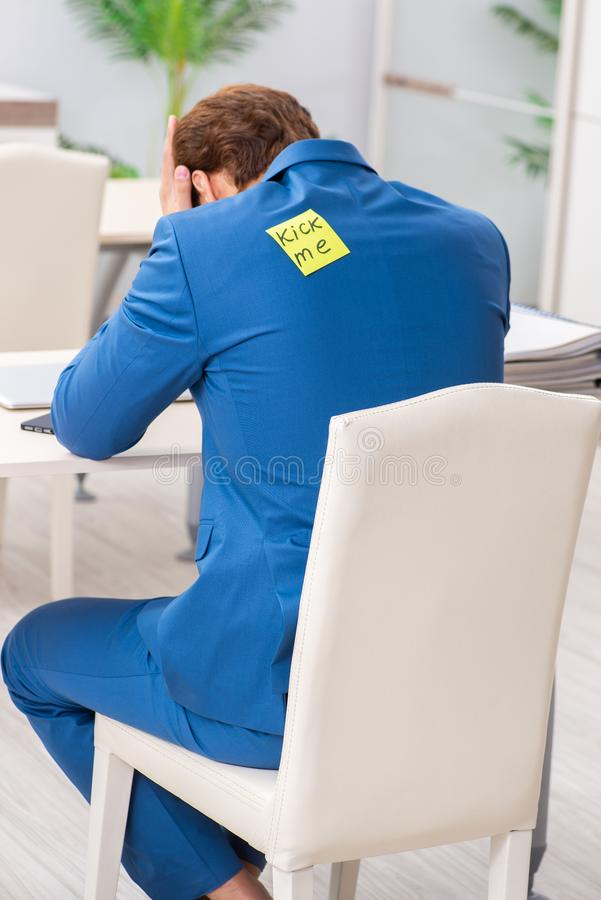 The office prank with kick me message on sticky note. Office prank with kick me message on sticky note stock photography
