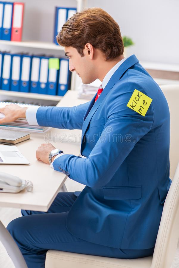 The office prank with kick me message on sticky note. Office prank with kick me message on sticky note royalty free stock photos