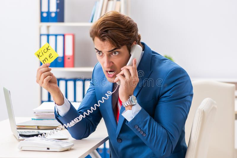 The office prank with kick me message on sticky note. Office prank with kick me message on sticky note stock photos