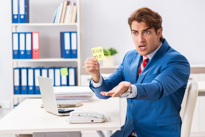 The office prank with kick me message on sticky note. Office prank with kick me message on sticky note stock photo