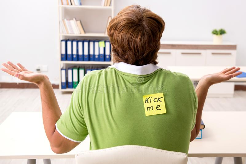 The office prank with kick me message on sticky note. Office prank with kick me message on sticky note royalty free stock image
