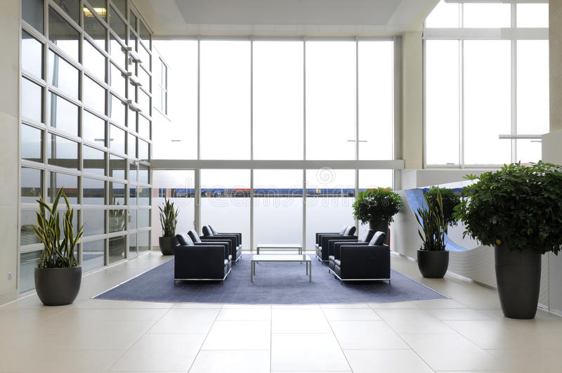 Office reception. The interior of a large office reception with seating plants and large smoked glass windows