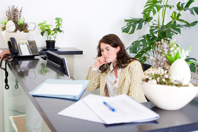 Office receptionist. Young female office receptionist talking on phone royalty free stock photography