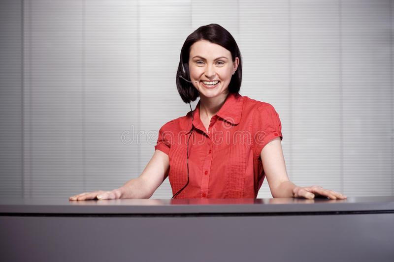 Office receptionist in a red blouse, smiling royalty free stock photography