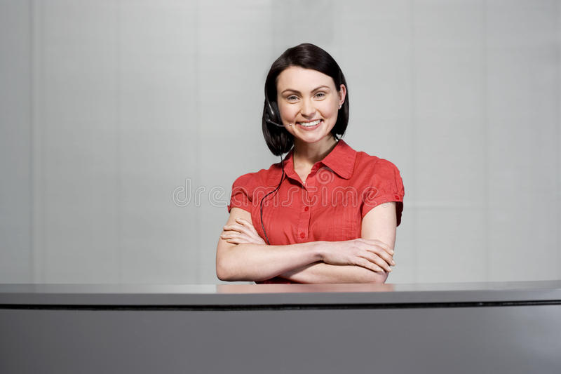Office receptionist in a red blouse, smiling stock images