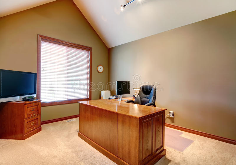 Office room with high vaulted ceiling. Furnished office room with olive walls, white high vaulted ceiling. View of oak desk with chair and TV on the cabinet royalty free stock photos