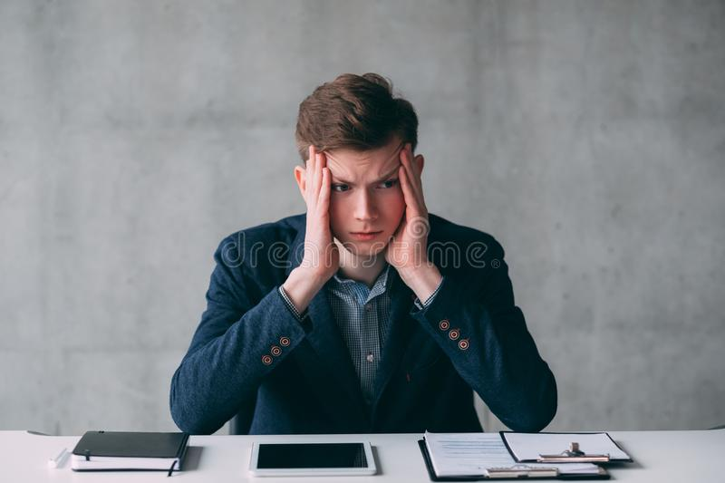 Office routine deadlines stressed young manager. Office routine and deadlines. Portrait of stressed out young manager sitting at office desk. Copy space stock images