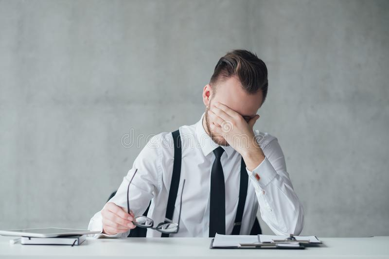 Office routine deadlines stressed young manager. Office routine and deadlines. Portrait of stressed out young manager sitting at office desk. Copy space stock photography