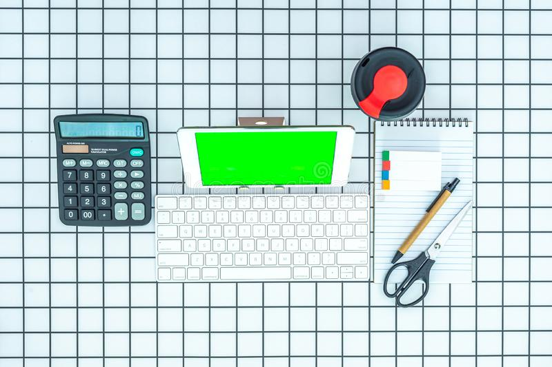 Stationery supplies with green screen tablet on checked background royalty free stock photo