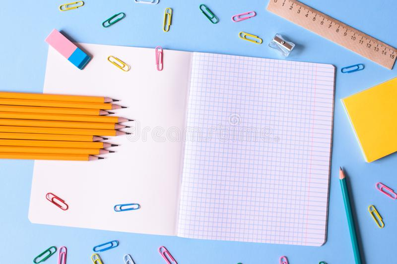Office and school supplies. Notebook in a cage with a pencils, eraser, ruler, paper clips and other office supplies on a blue background. Concept back to school royalty free stock image
