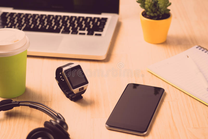 Office setup. Close up of two laptops, tablet and a smartwatch on a wooden office table. royalty free stock photography